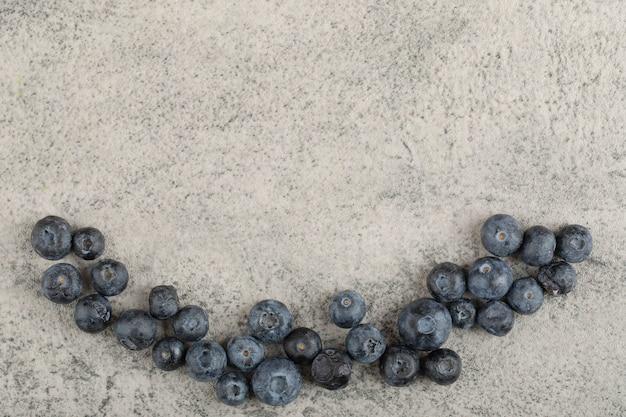 Bündel der frischen köstlichen blaubeeren, die auf steinhintergrund gelegt werden.