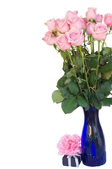 Bündel der frischen rosa rosen in der blauen vase mit geschenkbox lokalisiert auf weißem hintergrund