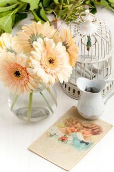 Bündel der gerberablume mit altem weinlesekäfig