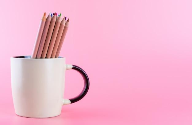 Bündel farbbleistifte in der kaffeetasse auf rosa kopienraum