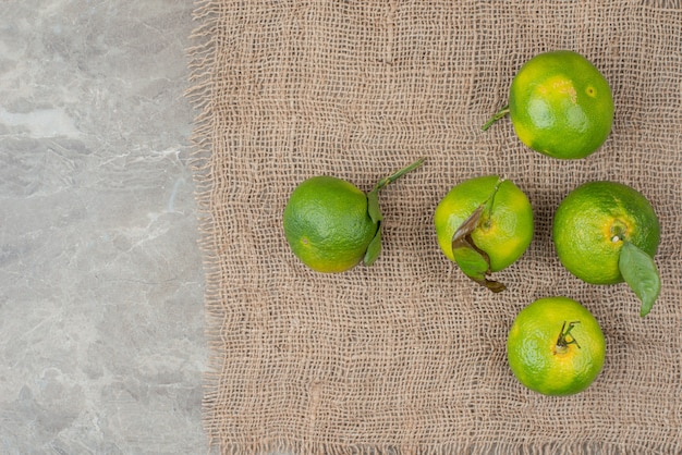 Bündel frische grüne mandarinen auf sackleinen.