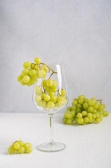 Bündel frische grüne trauben serviert im weinglas auf weißem holztisch für die herstellung von wein?