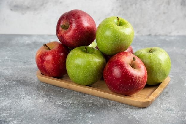 Bündel frische grüne und rote äpfel auf holzplatte gelegt.