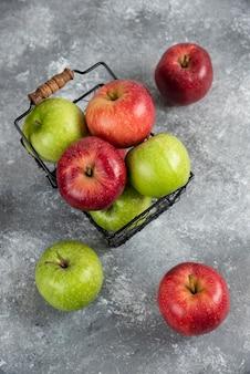 Bündel frische grüne und rote äpfel in metallkorb gelegt.