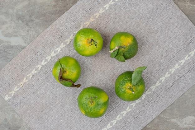 Bündel frische mandarinen auf grauer tischdecke.