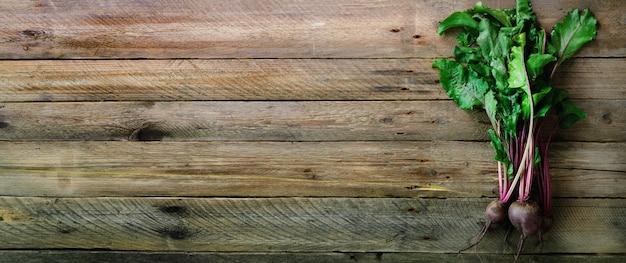 Bündel frische organische rote-bete-wurzeln auf hölzernem hintergrund. konzept der diät, rohe, vegetarische mahlzeit.