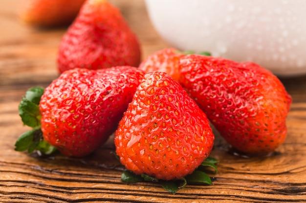 Bündel frischer erdbeeren auf holzbretthintergrund