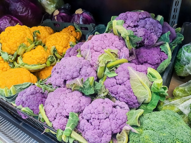 Bündel frischer gelber, lila und grüner blumenkohlköpfe auf dem bauernmarkt.