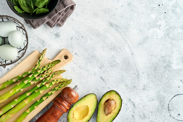 Bündel frischer grüner bio-spargelspinat, avocado, hühnereier, pfeffergewürz und mit schneidebrett auf grauem hintergrund, draufsicht. essen, das hintergrund mit kopienraum kocht.