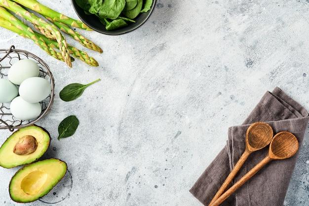 Bündel frischer grüner bio-spargelspinat, avocado, hühnereier und pfefferwürze auf grauem hintergrund, draufsicht. essen, das hintergrund mit kopienraum kocht.