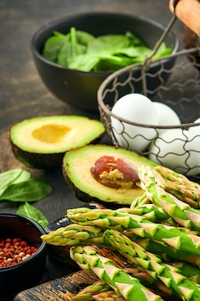 Bündel frischer grüner bio-spargelspinat, avocado, hühnereier und pfefferwürze auf schwarzer alter holzoberfläche, draufsicht. essen kochen mit kopierraum.