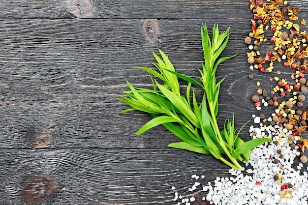 Bündel frischer grüner estragon mit salz, pfeffer, bockshornkleesamen gegen ein schwarzes holzbrett