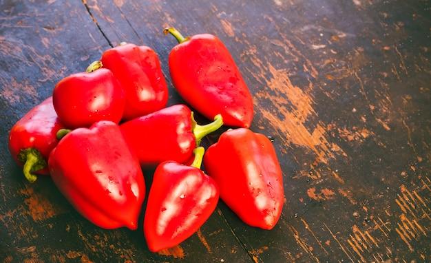 Bündel frischer reifer roter paprika auf einer alten schwarzen holzgrungeoberfläche