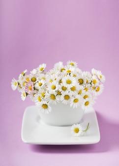 Bündel gänseblümchen in einer weißen vase auf rosa hintergrund. dekoration mit wilden blumen.