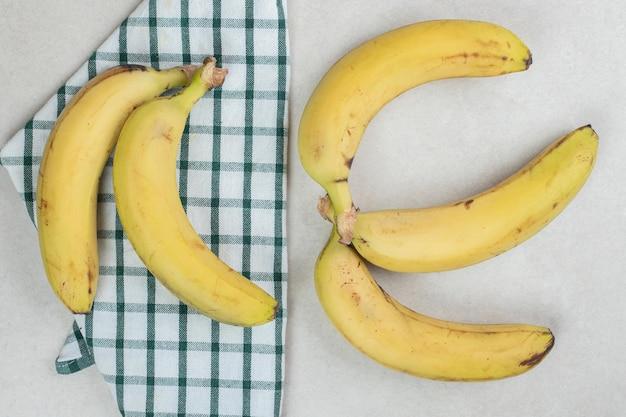 Bündel gelbe bananen auf gestreifter tischdecke