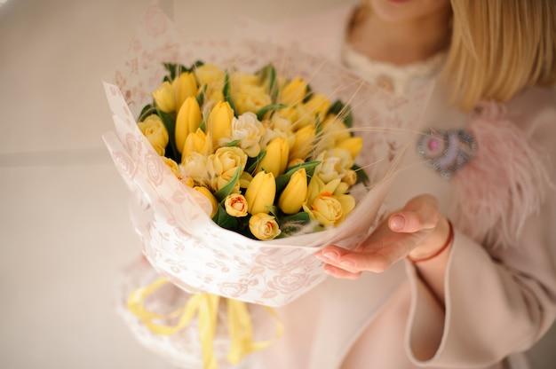 Bündel gelbe tulpen in den händen des mädchens