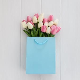 Bündel gelbe tulpen in der kühlen blauen einkaufstasche