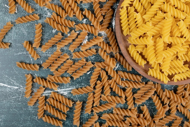 Bündel gelbe und braune fusilli-nudeln auf blauem hintergrund. hochwertiges foto