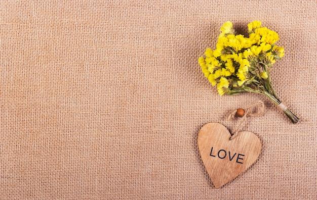 Bündel gelber blumen und hölzernes herz auf natürlichem leinenhintergrund. romantisches konzept.