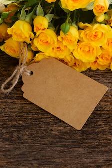 Bündel gelber rosengrenze auf holz mit leerem papierschein