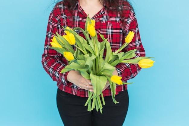 Bündel gelber tulpen auf frauenhänden auf blauer oberfläche