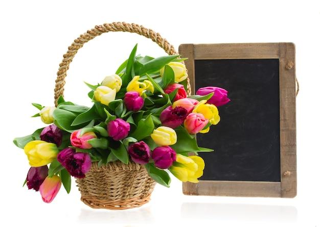 Bündel gelber und lila tulpenblumen im korb mit schwarzer tafel lokalisiert auf weißer wand