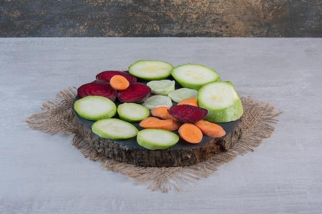 Bündel geschnittenes rohes gemüse auf holzstück. hochwertiges foto