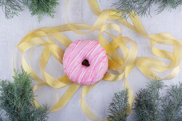 Bündel goldener bänder und eines donuts auf weißem hintergrund.