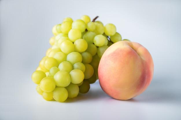 Bündel grüne trauben und ein rosa pfirsich isoliert auf weiß
