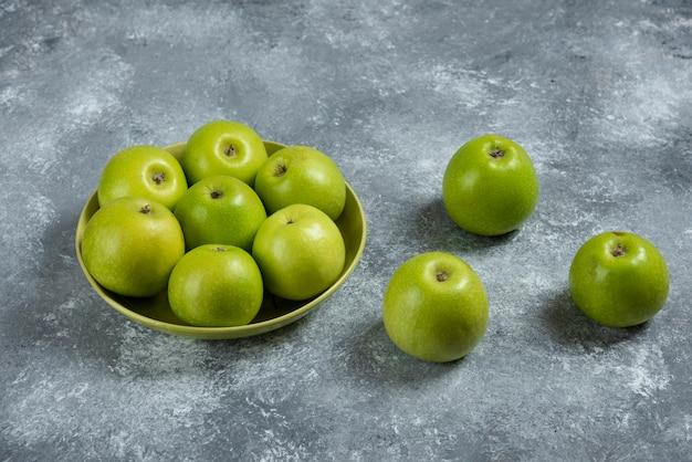 Bündel grüner äpfel in grüner schüssel.