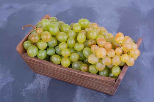 Bündel grüner trauben in einem holztablett.