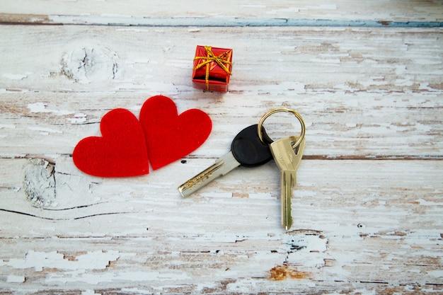 Bündel hausschlüssel mit herzen auf hölzernem hintergrund, valentinstaggeschenk