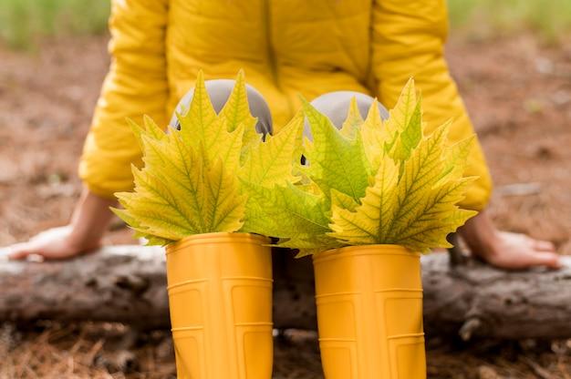 Bündel herbstblätter in gelben regenstiefeln