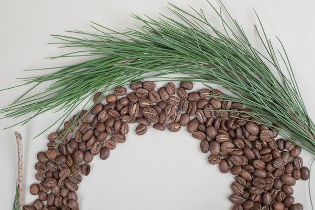 Bündel kaffeebohnen mit zweig auf grauer oberfläche