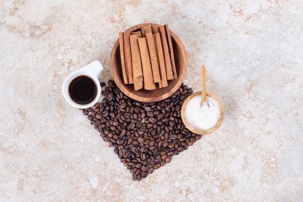 Bündel kaffeebohnen, zimtstangen, zucker und eine tasse kaffee