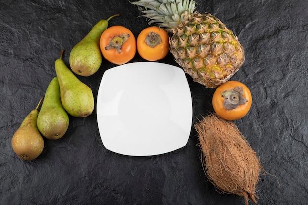 Bündel köstlicher frischer früchte und leerer teller auf schwarzer oberfläche