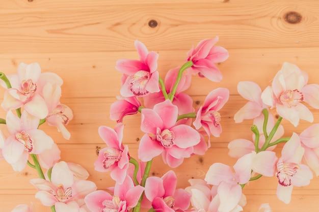 Bündel künstliche blühende orchidee blüht auf hölzernem hintergrund. innenausstattung.