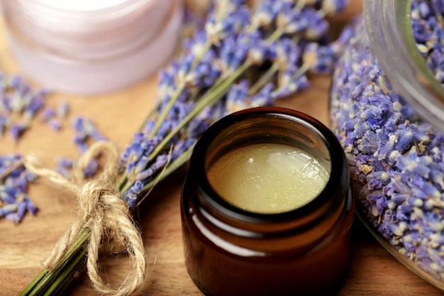 Bündel lavendel und kosmetischer topf auf einem holztisch