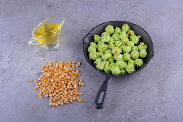 Bündel maiskörner, glas öl und eine bratpfanne mit kandiertem popcorn auf marmorhintergrund. foto in hoher qualität