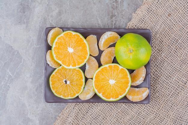 Bündel mandarinenscheiben und -segmente auf schwarzem teller.