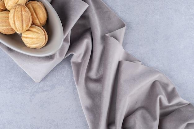 Bündel mit karamell gefüllte keksbällchen in einer schüssel auf marmortisch.