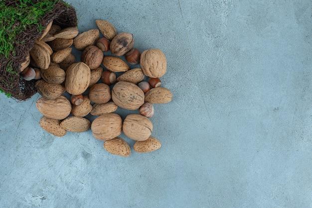 Bündel nüsse, die aus einer ausgefallenen schüssel auf marmor gießen. Kostenlose Fotos