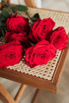Bündel oder rote rosen auf einem holzstuhl