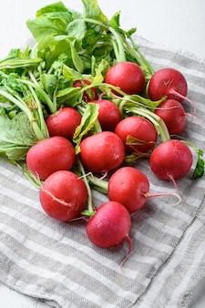 Bündel radieschen. frisch geernteter, lila bunter rettich. wachsender rettich. wachsendes gemüse. gesunder lebensmittelhintergrundsatz, auf weißem steinhintergrund