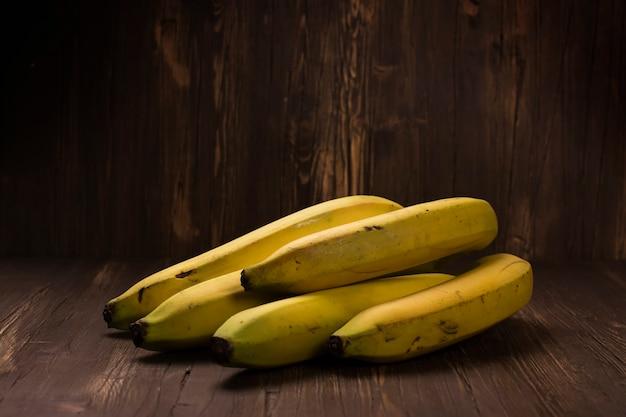 Bündel reife bananen über rustikalem hölzernem hintergrund