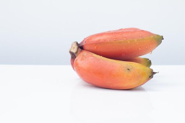 Bündel reife cavendish banane oder rote bananen tragen auf weißer tabelle und weißem hintergrund früchte