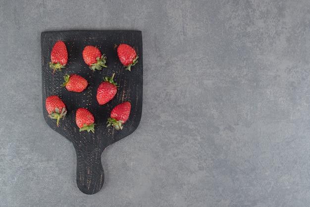 Bündel reife erdbeeren auf holzbrett. foto in hoher qualität