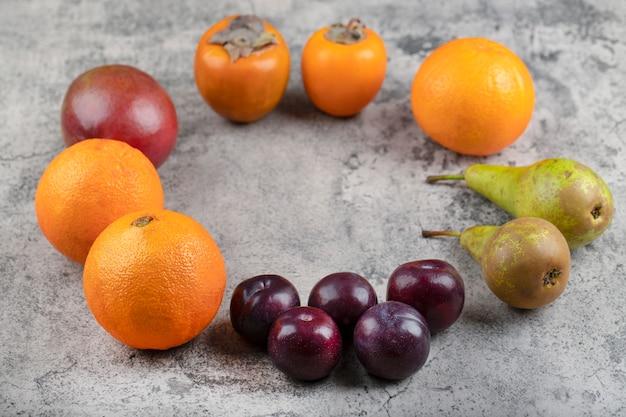 Bündel reifer frischer früchte, die auf steinhintergrund gelegt werden.