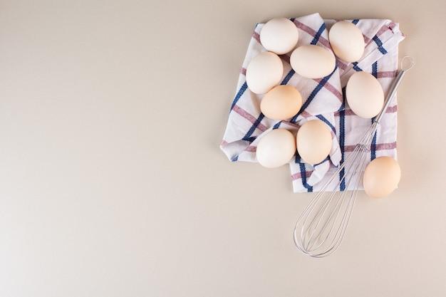 Bündel rohe bio-eier mit schnurrbart auf beigem tisch.