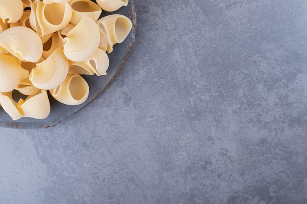 Bündel rohe muschelnudeln auf holzstück.